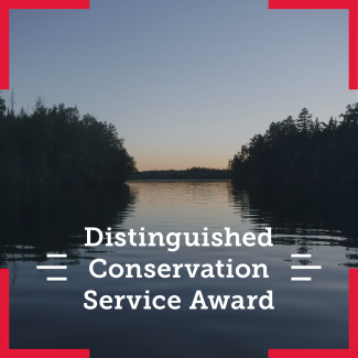 Scenic view of water and trees. The overlying text says Distingished Conservation Service Award
